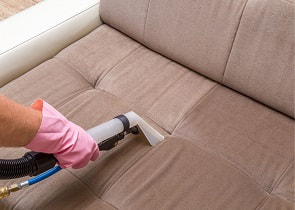 Picture of a brown couch being cleaned by a Fremont Carpet Cleaner Upholstery Cleaning technician. Shows how it looks before and after cleaning.